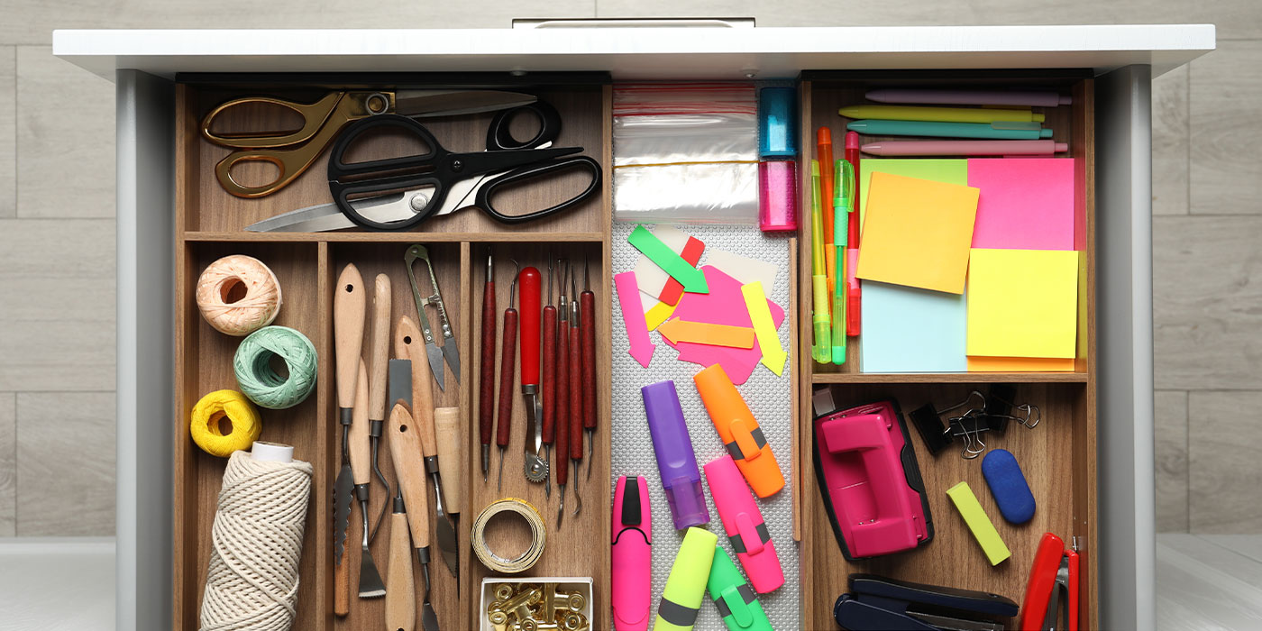 An open drawer filled with stationary and organised with wooden dividers