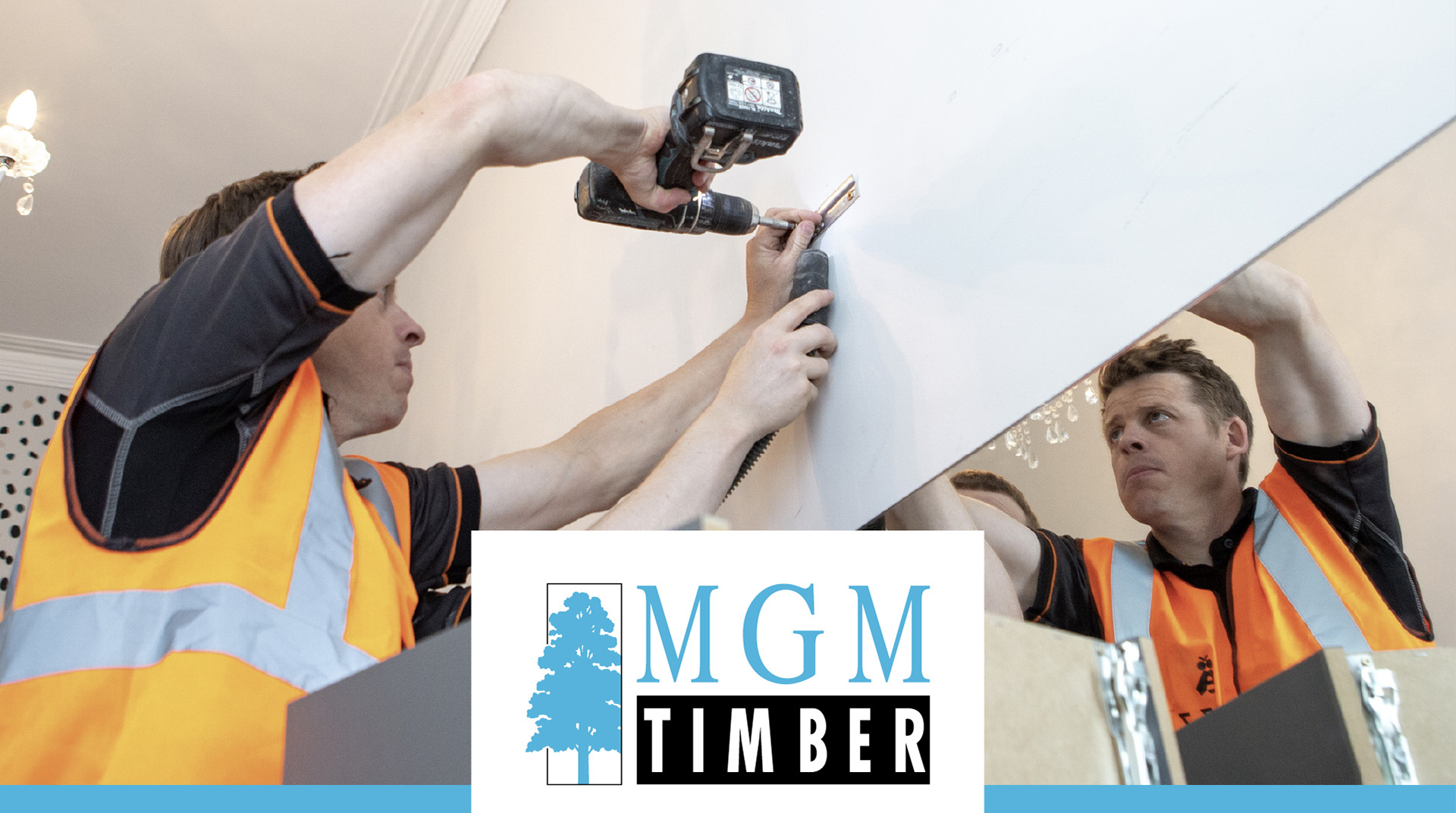 Two Buzz hive fitters installing holding systems for Buzz home office furniture, with the MGM Timber logo in front who work in Partnership with Buzz home office